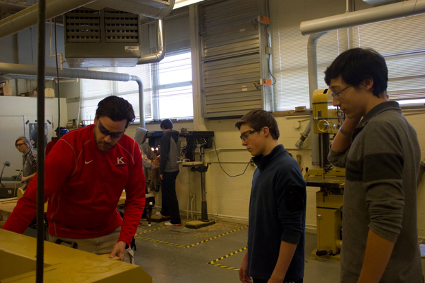 """Mike Brown demonstrates how to use a planer in the woodshop for James Strevey, sophomore, and Henri Friedeck, junior. """"He's a good teacher who is really interactive,"""" Friedeck said."""