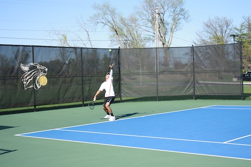 Kylel Gillam, senior, starts off his match against Westminster with a serve.