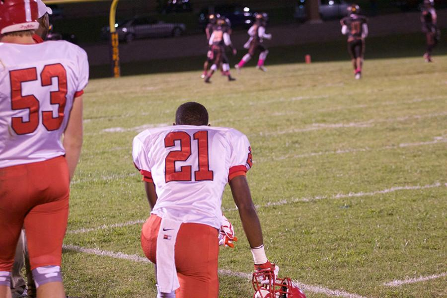 Safety Antonio Phillips, junior, kneels as his watches the current play