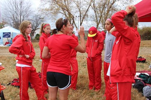 Coach Woodard gives the 7 varsity runners a motivational talk before they head to the starting line.