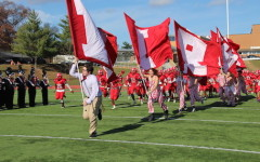 Pep Nation and the  football team run onto the field before the game to get the crowd pumped up.