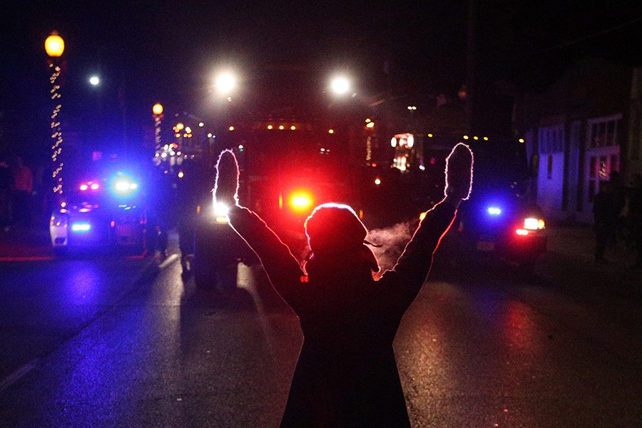 A protester raises her hands in the street as police use tear gas to try to take control of the scene near a Ferguson Police Department squad car after protesters lit it on fire on Tuesday, Nov. 25, 2014, in the wake of the grand jury decision not to indict officer Darren Wilson in the shooting death of Ferguson, Mo., teen Michael Brown. (Anthony Souffle/Chicago Tribune/TNS)