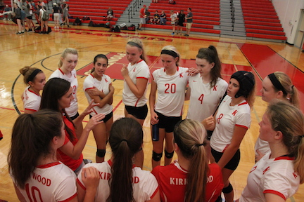 Julie Goodmann, head varsity girls' volleyball coach, talks to the team after their win against Parkway North.