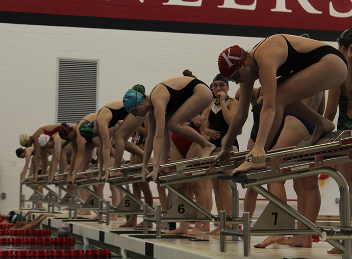 """The girls' swim and dive team members line up on the blocks at tryouts. """"I've learned a lot from swimming,"""" Maddie Clark, junior, said. """"I learned how to be an individual in a group because swimming is a team sport."""""""