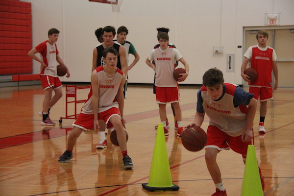 Ryan Tyrell and Preston Salazar, sophomores, weave in and out of cones working on their ball handling skills.