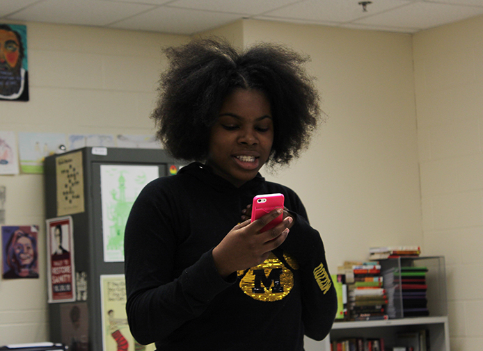 Sha%E2%80%99Diya+Tomlin%2C+junior%2C+reads+her+poetry+off+her+phone.+%E2%80%9CI+think+it%E2%80%99s+great+how+%5Bstudents%5D+learn+to+write+for+themselves%2C+and+I+think+it%E2%80%99s+very+inspiring+to+new+people+that+come+in+and+hear+what+their+peers+have+to+say%2C%E2%80%9D+Dominic+Pioter%2C+english+teacher+and+K+Word+sponsor%2C+said.+%E2%80%9CIt+shows+how+powerful+writing+can+be.%E2%80%9D+%0A