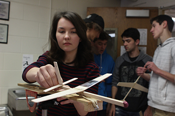 "Catherine Wright, sophomore, inspects her glider before launch. Wright chose Aerospace Engineering while flipping through the course description book because she loves learning about planes. ""My favorite part of the class is getting to make your own plane, instead of having to test ones that other people have made,"" Wright said. ""[I love that] each plane is unique."""