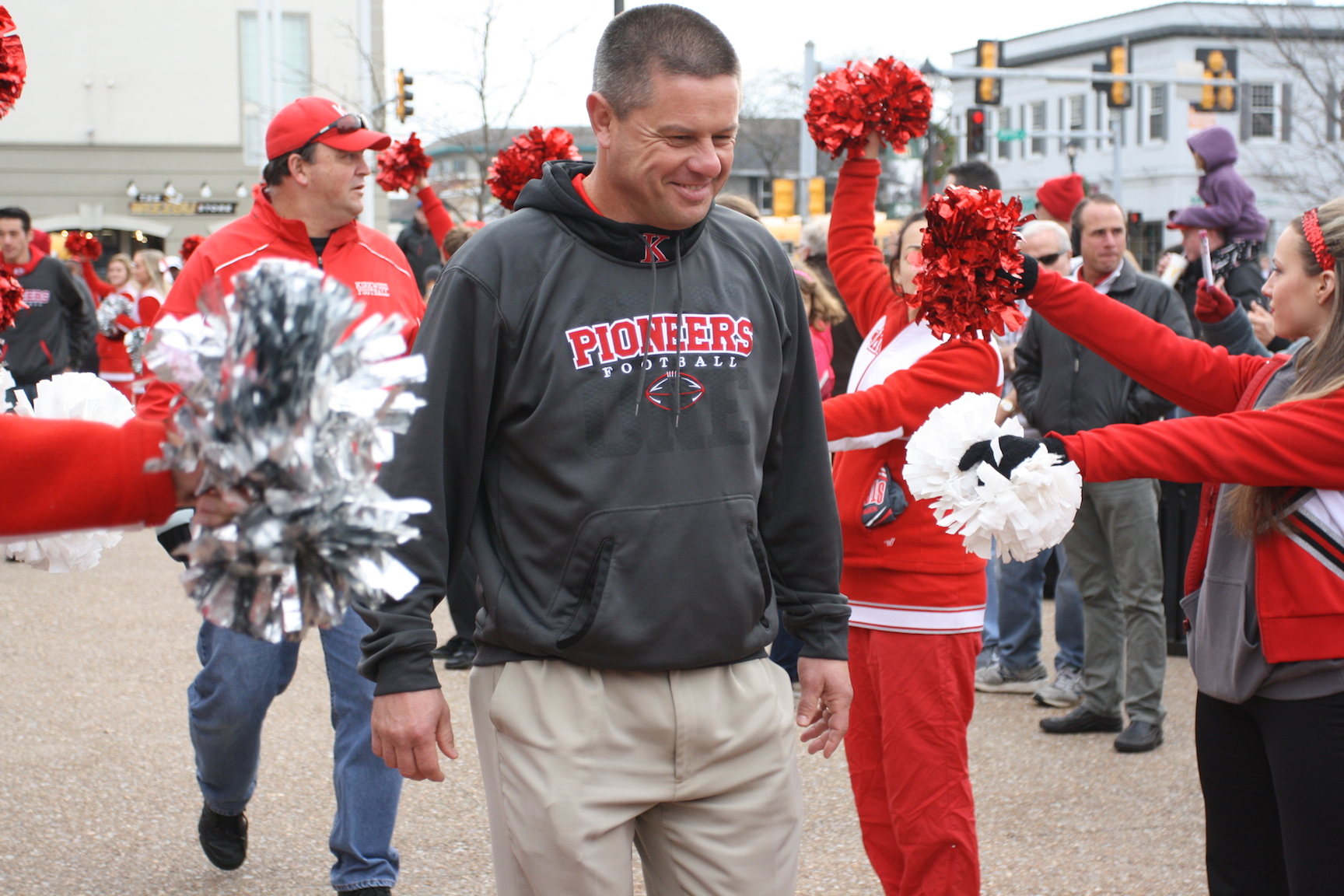 Farrell Shelton, head varsity football coach, smiles as he walks through a tunnel made by the pommies and cheerleaders, making his way to the podium.