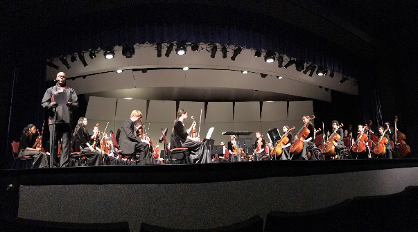 """Patrick Jackson, orchestra teacher, makes an introductory speech while the symphonic orchestra waits to play their first song at the 2016 winter concert Dec. 7. Jackson included his goodbyes to the audience since this is his last year teaching at KHS before retiring. """"It was great hearing everyone share their memories and stories about [Mr. Jackson's] long teaching career,"""" Hailey Chellis, junior and member of the symphonic orchestra, said. """"[Mr. Jackson] seemed really pleased with the concert. [The concert] was a phenomenal close to his time here at Kirkwood."""""""