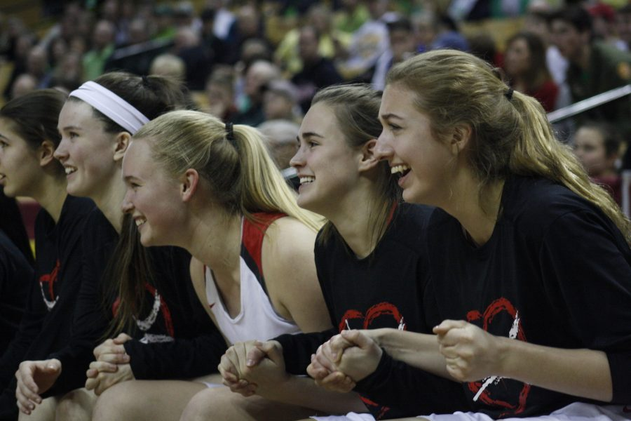Abby Ludbrook, sophomore, Emily Kreidler, junior, Kate Jozwiakowski, freshman, and Ashley Anderson, junior, hold hands and cheer for their teammates in the first of two overtimes.