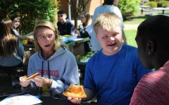 Jacob Martin, junior, eats pizza with Kat Moore and Tyresse Norris, seniors.