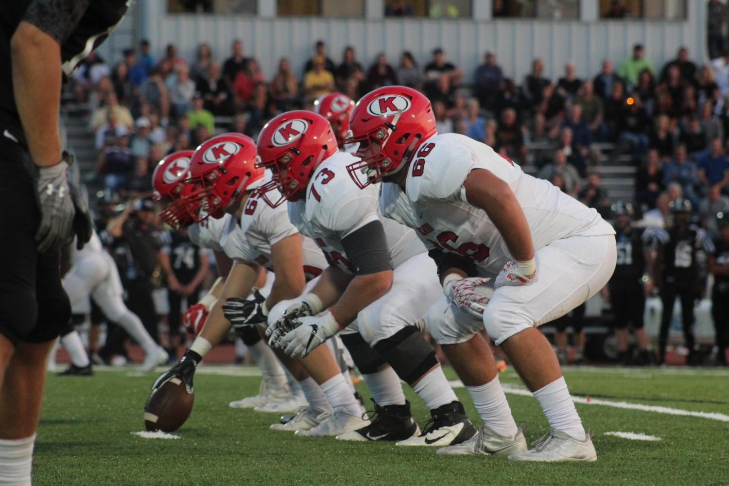 Football players prepare to spike the ball.