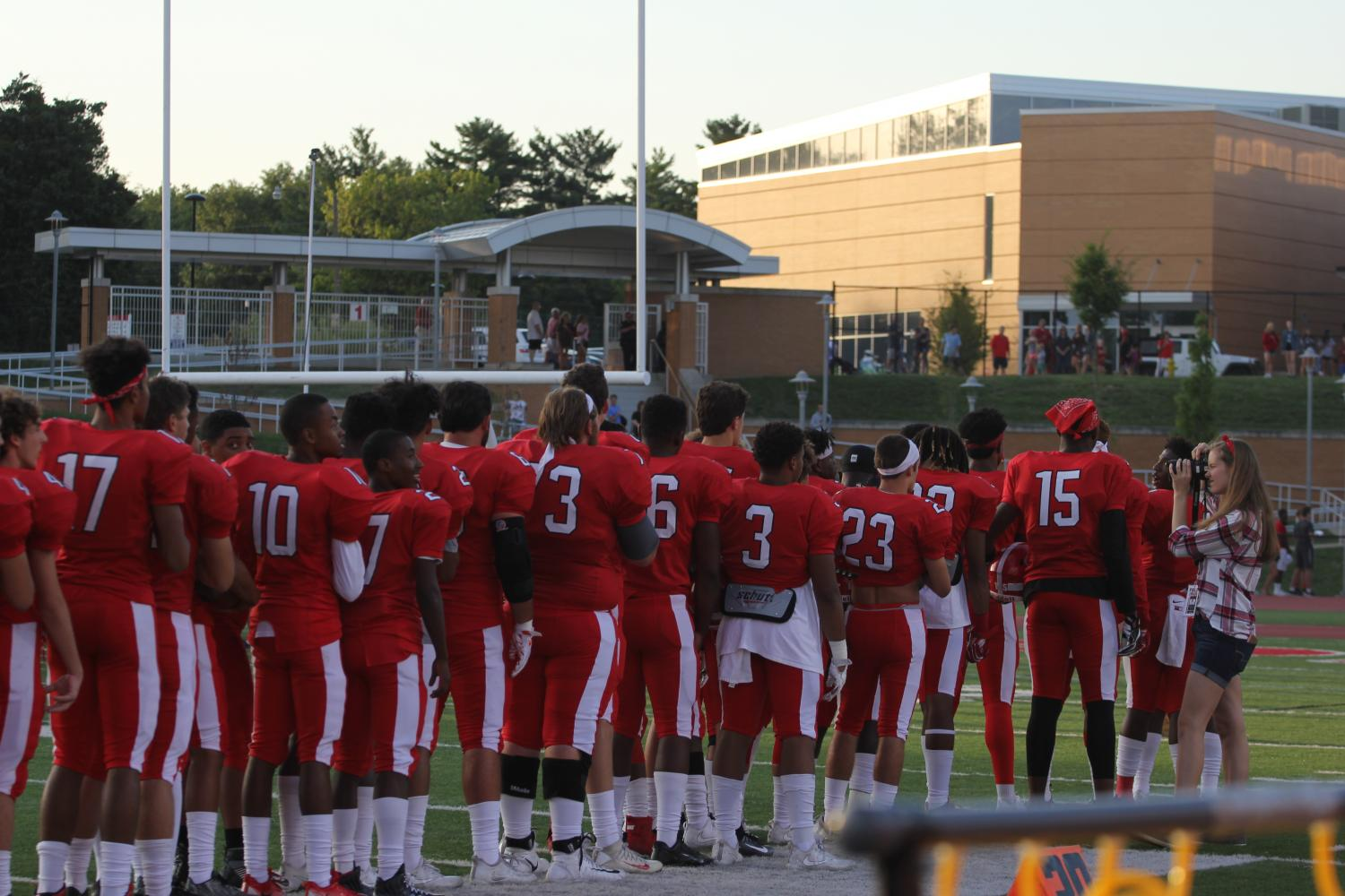 KHS+varsity+football+players+stand+for+the+National+Anthem+before+the+game+begins.