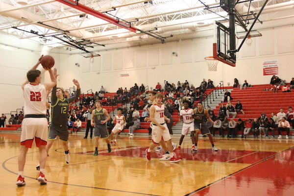 Alex Zirges, junior, shoots a three point shot from the corner of the court.