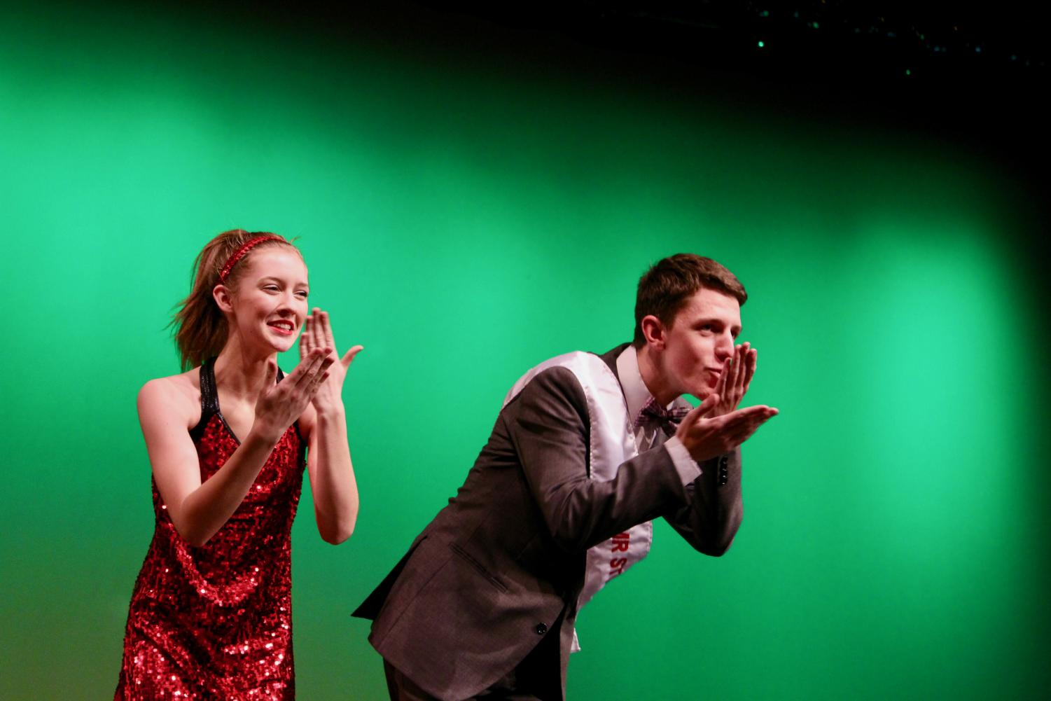 Lindsay+Kocher%2C+sophomore%2C+and+Tim+Knight%2C+senior%2C+blow+kisses+to+the+crowd+during+the+formal+wear+segment.