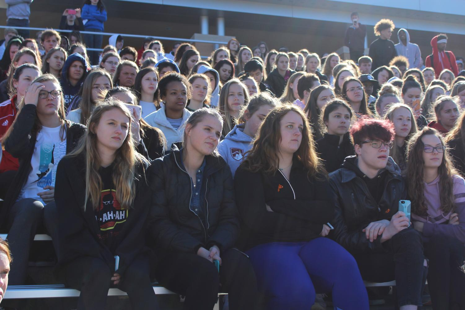 Students+sit+in+the+bleachers+and+listen+to+speakers.