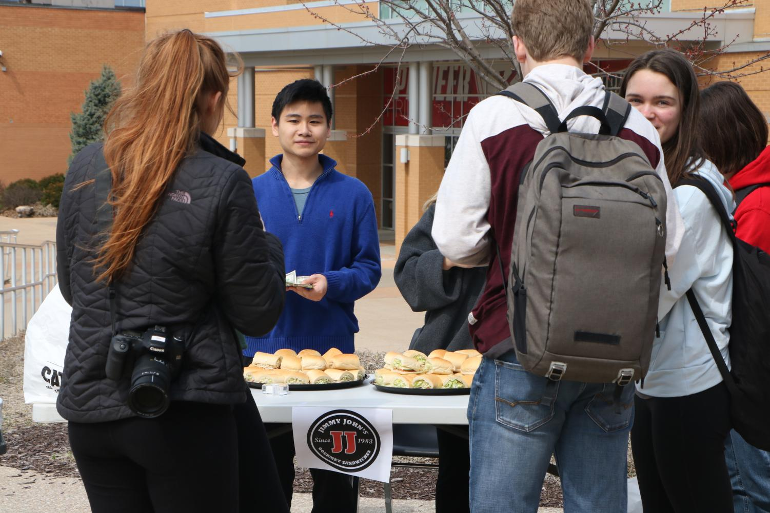Jimmy+Tang%2C+senior%2C+hands+out+sandwiches+donated+that+Jimmy+Johns+donated+to+the+event.+
