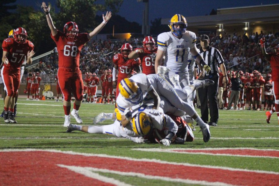 Quinton Costello, junior, raises his arms in reaction to a teammate being tackled.