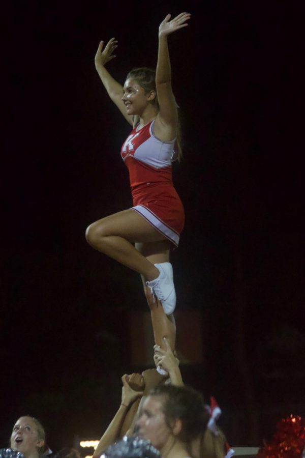 Madison Declue, senior, pulls a lib while stunting with the cheer team.