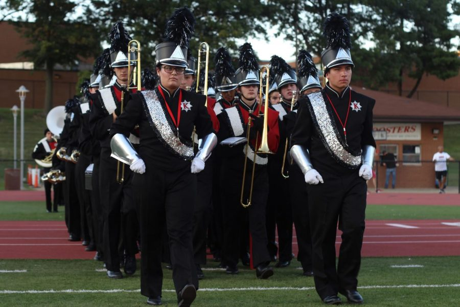Drum+majors+Claire+Boysen%2C+senior%2C+and+Ryan+Bowermaster%2C+junior%2C+lead+the+band+onto+the+field+before+playing+the+national+anthem.