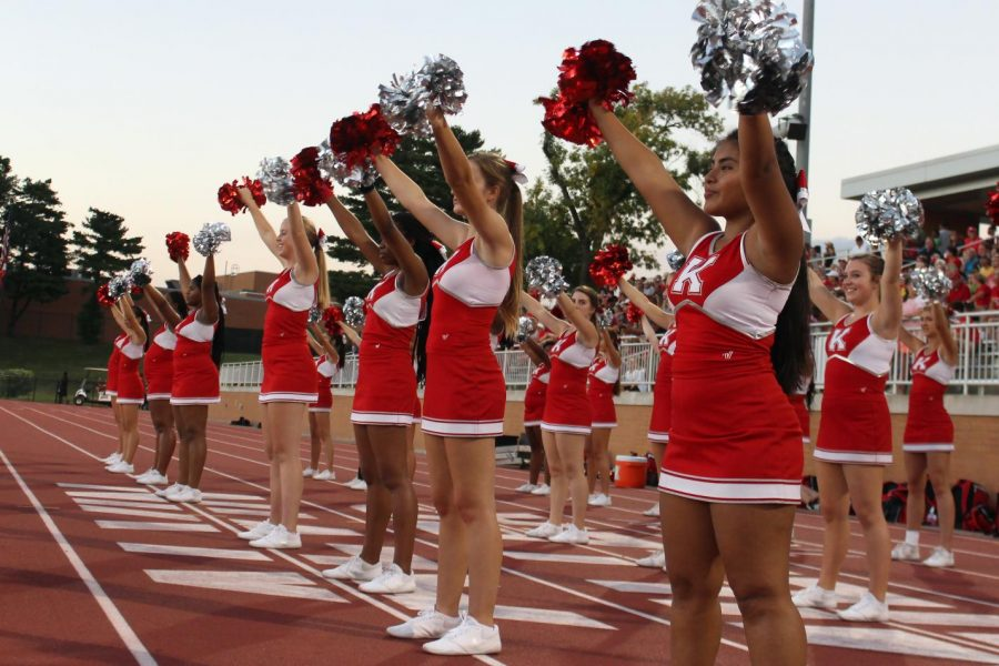 Cheerleaders support their team with chants on the sidelines.