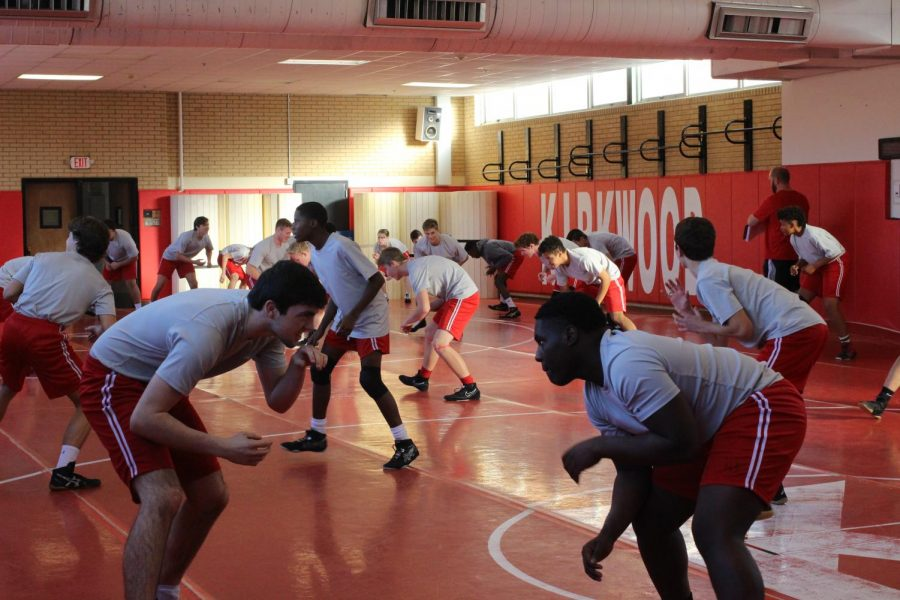 Varsity wrestlers warm up by practicing stances and transitions.