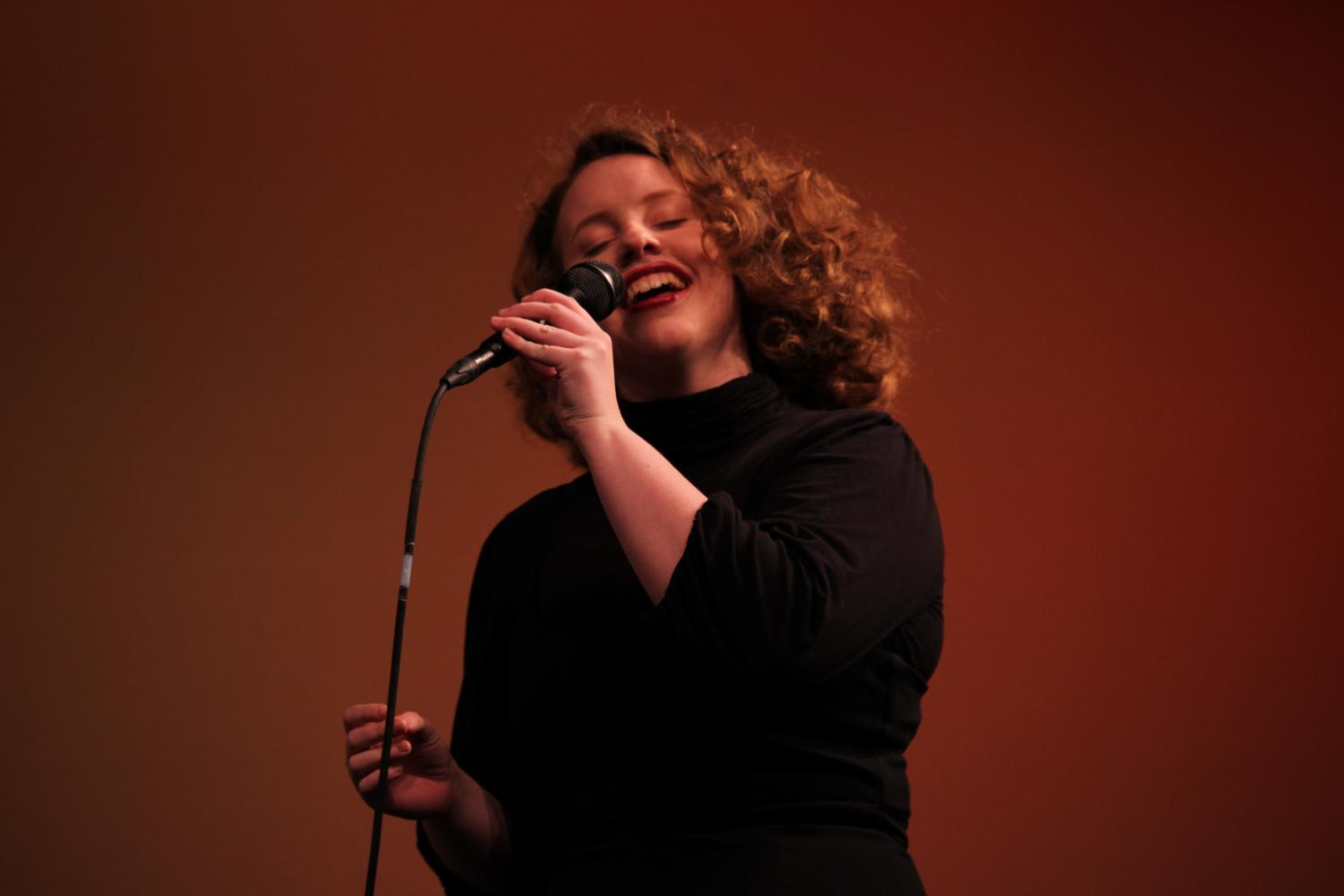 Cece+Herwig%2C+senior%2C+holds+the+microphone+while+she+hums+jazz+melodies.