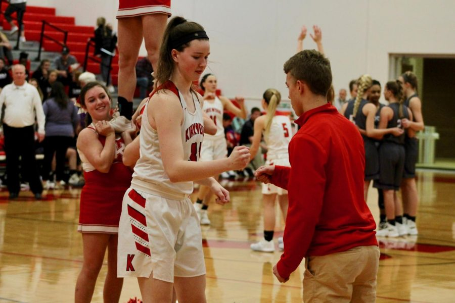 Abby+Ludbrook%2C+senior%2C+does+her+handshake+with+Aiden+McGee%2C+junior+and+varsity+girls%27+basketball+manager+as+they+introduce+the+starting+lineup.