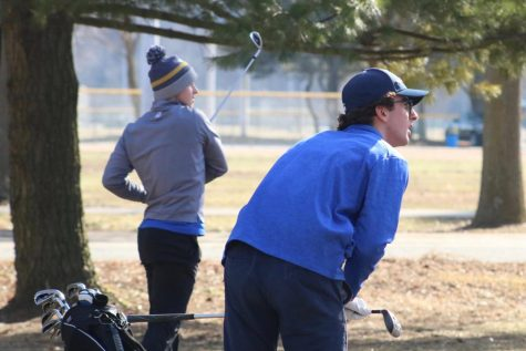 Hunter Bickel and Eli Boshara, seniors, watch the ball go down the fairway.