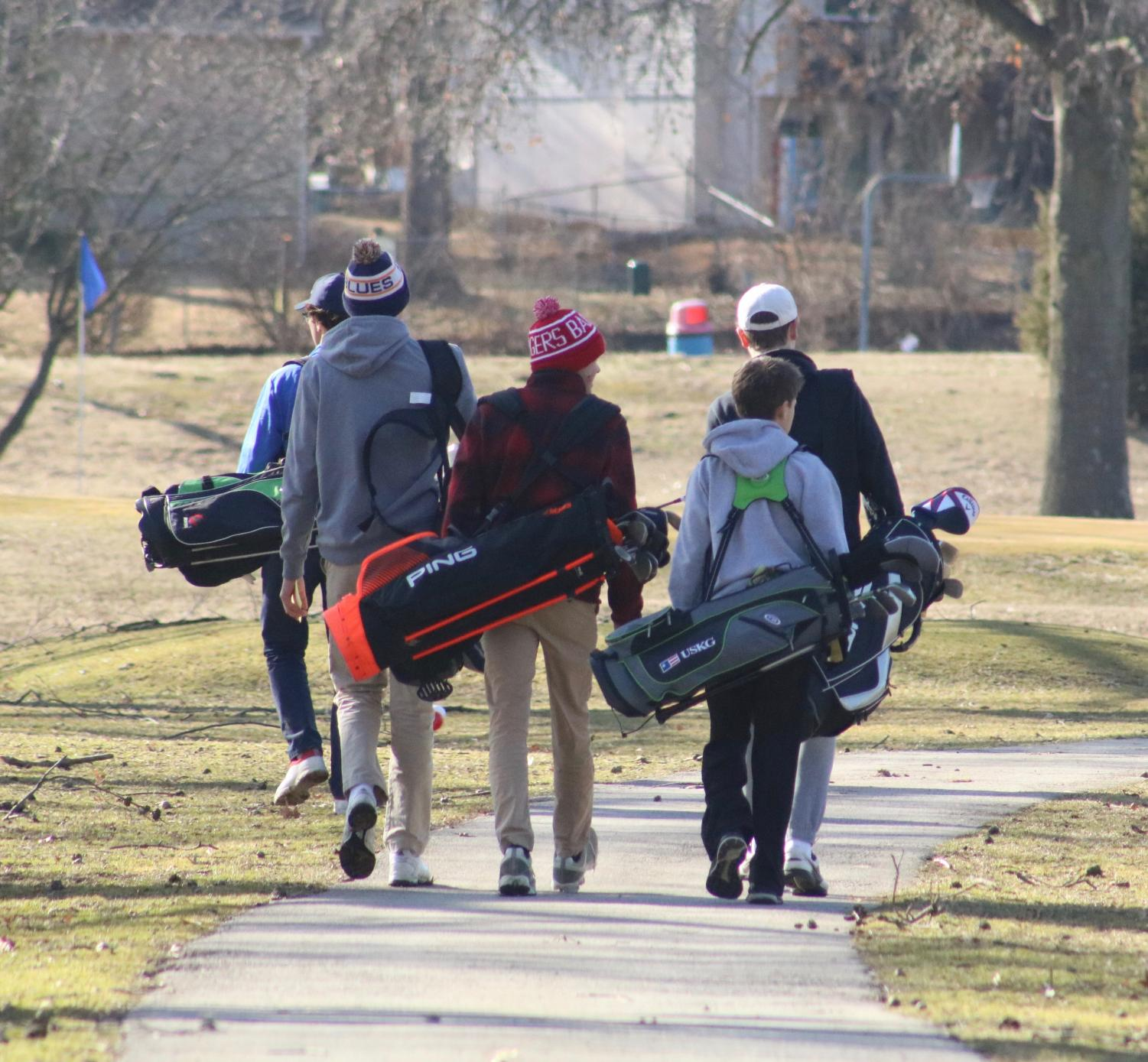 Golfers+walk+down+the+cart+path+to+their+starting+tee.+