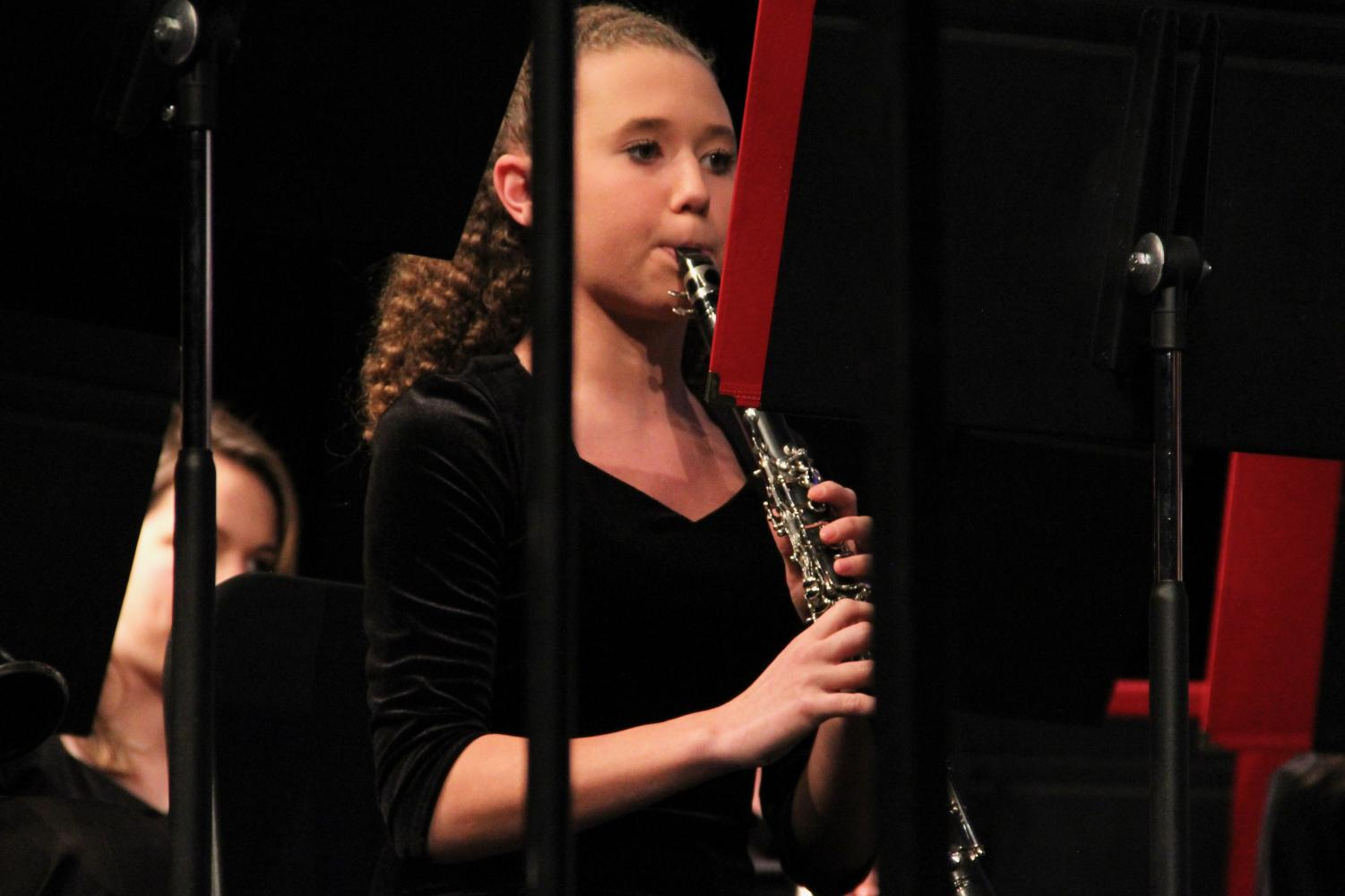 Isabella+Knopfel%2C+freshman%2C+focuses+on+her+sheet+music+as+she+plays+her+instrument.