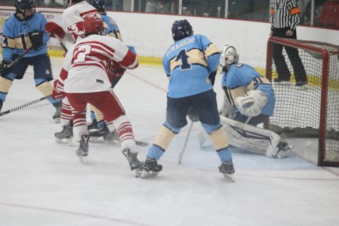 The Pioneers battle for the puck in front of the goal.