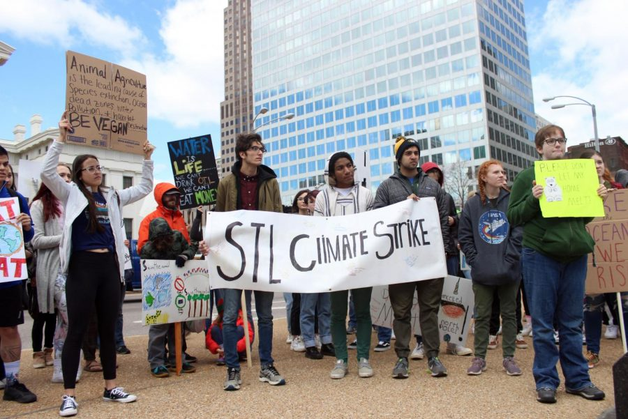 Strikers+hold+a+large+sign+that+reads+%22STL+Climate+Strike.%22