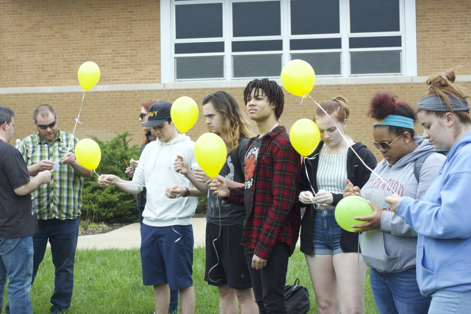 Students+tie+their+written+messages+to+their+balloons.