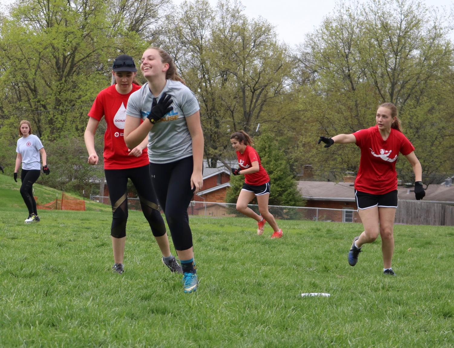 Katie+Hastings%2C+junior%2C+talks+to+teammates+as+she+picks+up+the+disc+after+the+turnover.+