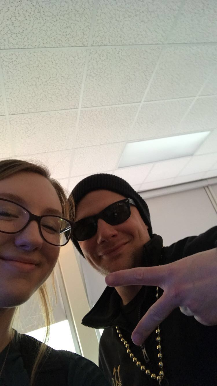Adam+Rowland%2C+English+teacher%2C+throws+up+a+peace+sign+while+posing+with+Cate+McCandless%2C+junior.