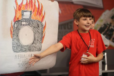Michael Simpkins, camper, explains why his group's logo is a camera on fire.