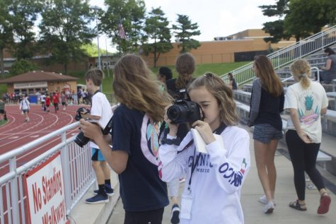 Taylor Coffman, camper, focuses a camera at the track.