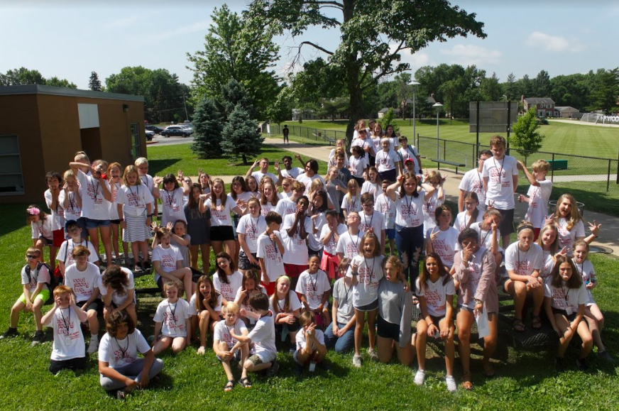 Campers and counselors gather outside for a silly group picture.