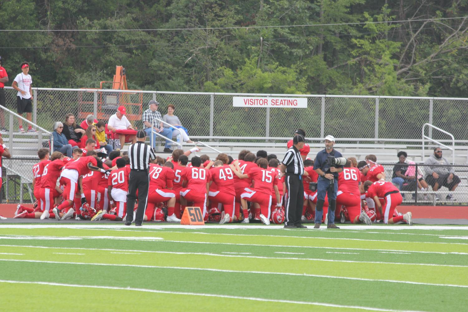 The+Pioneers+kneel+in+a+huddle+before+the+game.