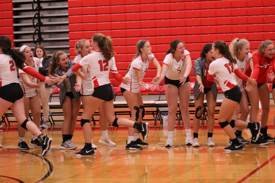 Varsity girls volleyball gets congratulated by the JV team after winning the game against Ursuline.