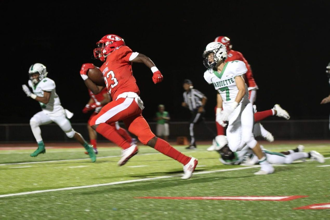 Senior wide receiver Melvin Simmons (23) beats Marquette's defense to score a 43-yard touchdown to give KHS a 14-7 lead late in the first half. Photo by Natalie Sweesy/Pioneer Yearbook.