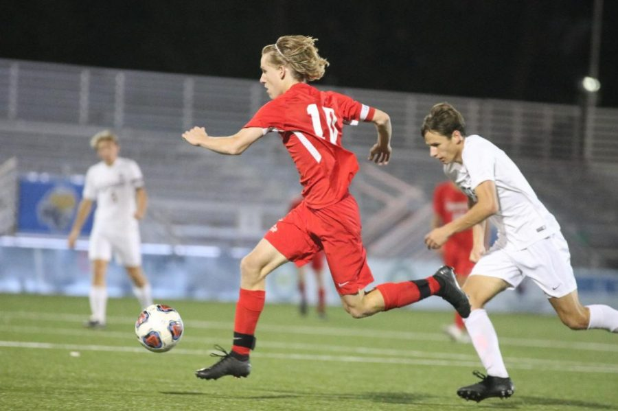 Sawyer Hardy, senior, strides through the air as he dribbles the ball towards the net.