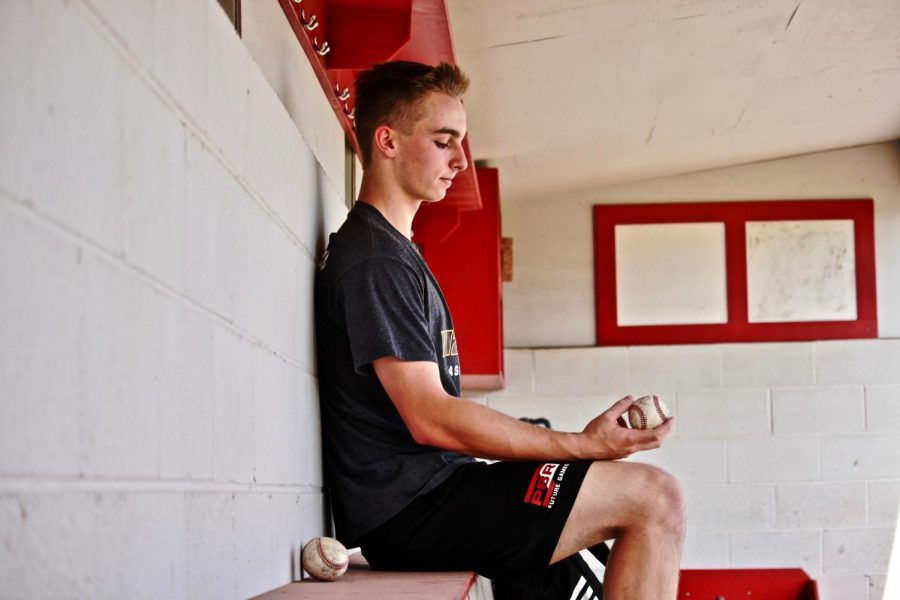 Sam Bryan, junior, sits inside Kirkwood High Schools home dugout.