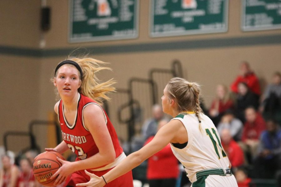 Tara Benham, sophomore, looks to pass the ball while getting around an opposing player.
