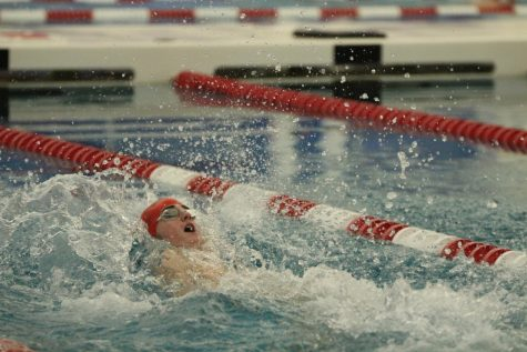 Wyatt Harris, sophomore, swims backstroke during a varsity swimming race.