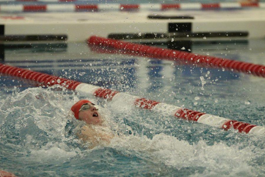 Wyatt Harris, sophomore, swims backstroke during a varsity swimming race.