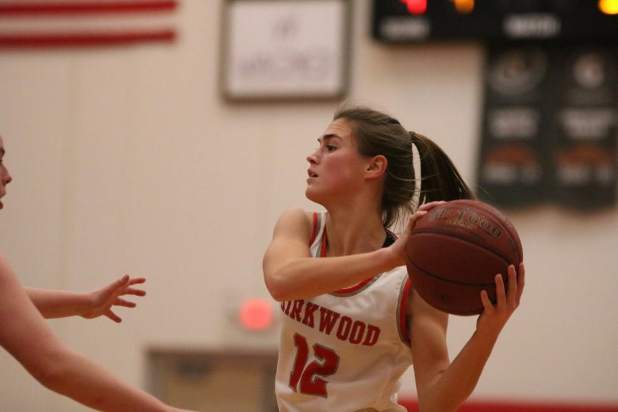 Kate+Jozwiakowski%2C+senior%2C+looks+around+a+competitor+to+pass+the+ball+to+a+teammate.