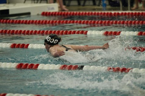 Alyssa Dennis, sophomore, swims her 100 butterfly, and breaks her own record for the 4th time.