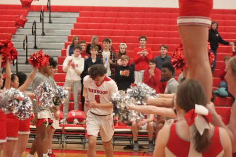 Landon Evans, senior, runs to the applause of cheerleaders and his team before the game.